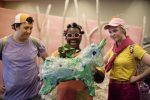 Lir and Darya are standing on either side of Nix, who is holding a unicorn she has made out of discarded plastic water bottles. The three of them look at the unicorn with admiration.